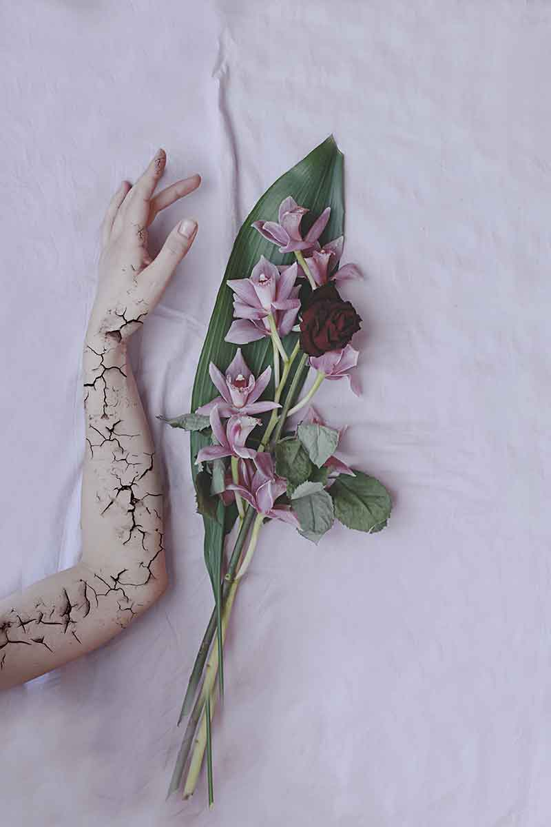 this photo shows a cracked arm with some flowers near it