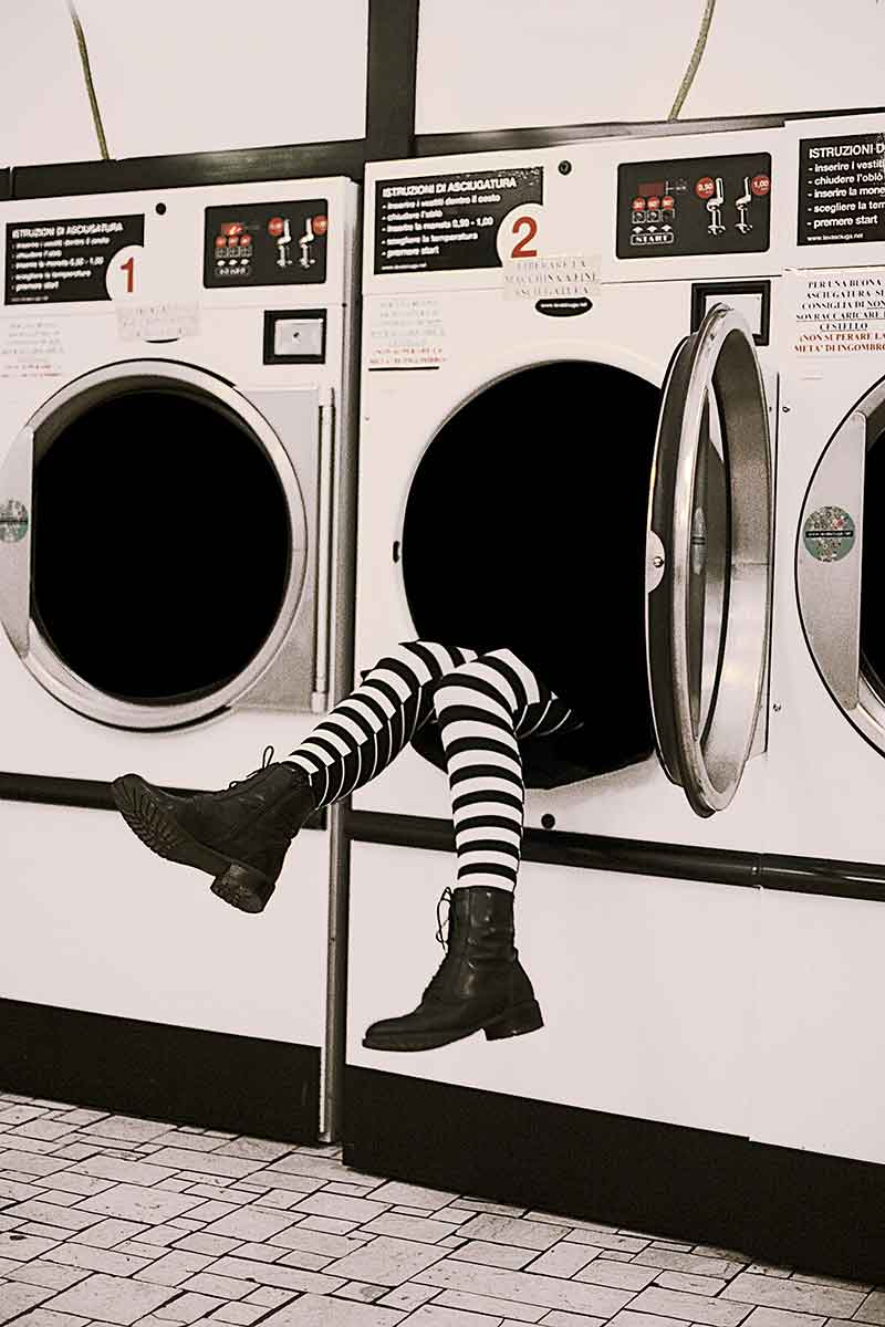 the image shows a woman that is fallen in the oblò of the washing machine